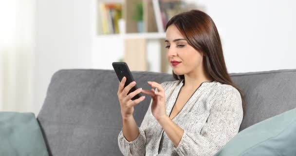 Photo Happy woman recording an audio note in a smart phone at home