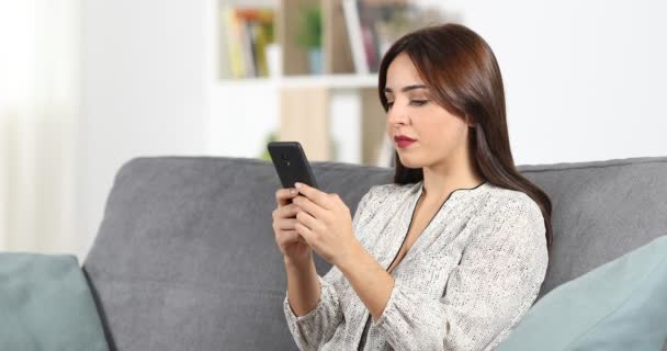 Surprised woman reading good news in a smart phone content sitting on a couch at home