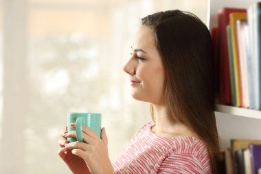 Side view portrait of a relaxed woman holding a coffee cup looking away at home