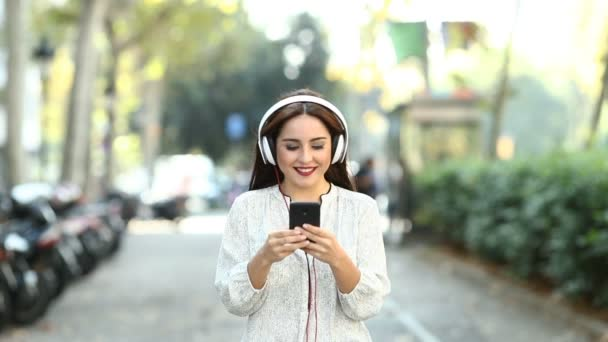 Front view of a happy woman walking towards camera listening to music with a smart phone recorded in slow motion