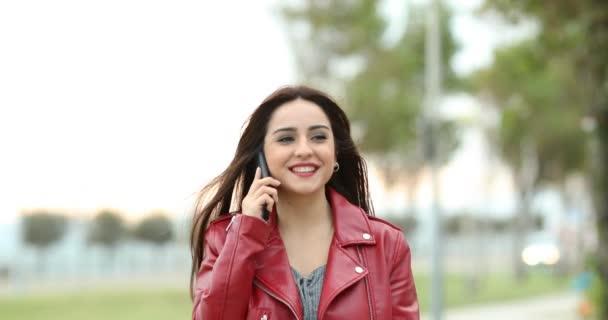 Vorderansicht einer glücklichen Frau, die in einem Park auf die Kamera zugeht und telefoniert