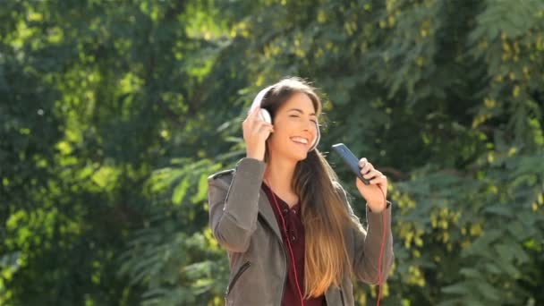 Slow motion of a funny teen listening to music singing and dancing in a park