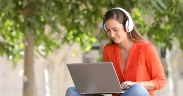 Koncentrált nő az e-learning a fejhallgatók és egy laptop, ül egy padon a parkban