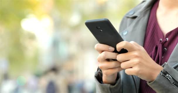 Közelkép a nő kezét textil egy szúró telefon-az utcán