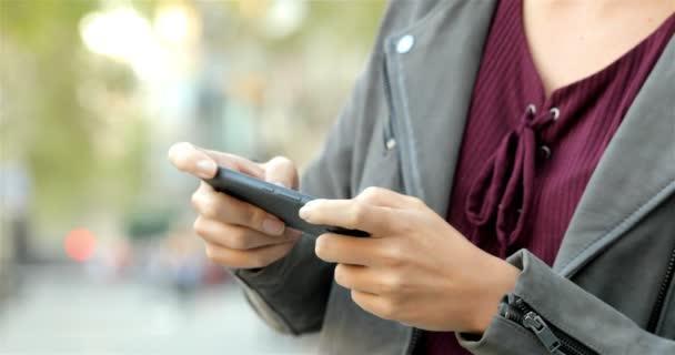 Közelkép a nő kezét, videó lejátszás game egy szúró telefon-az utcán