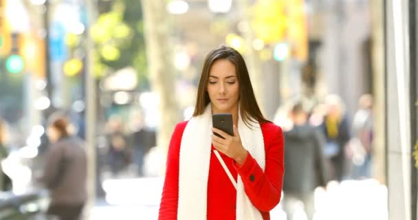 Front view portrait of a shocked woman walking towards camera reading online news on a smart phone in the street