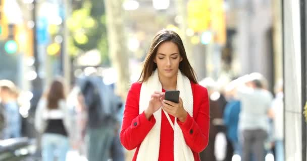 Front view of an excited woman walking towards camera receiving good news online on a smart phone in the street in winter