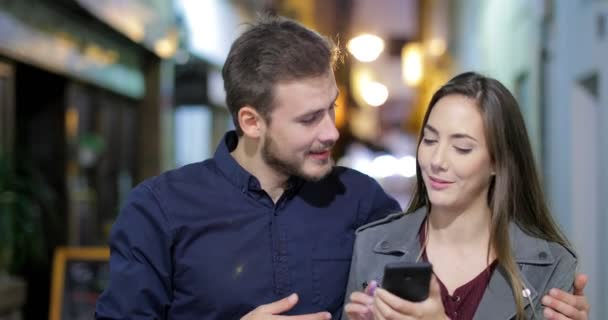 Front view of a happy couple walking using a smart phone in the night in the street of an old town