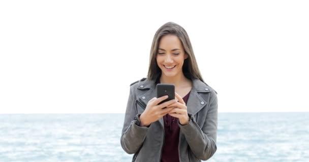 Elölnézet boldog nő használ egy okos telefon, a strandon