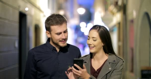 Front view of a happy couple browsing smart phone walking in the night in the street