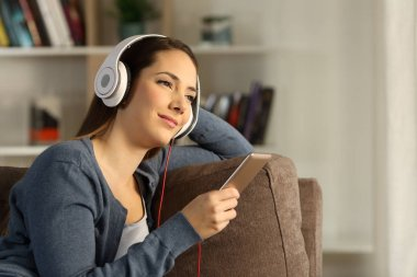 Relaxed woman listening chillout music sitting on a couch in the living room at home