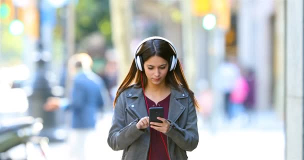 Front view of a happy teen listening to music dancing in the street