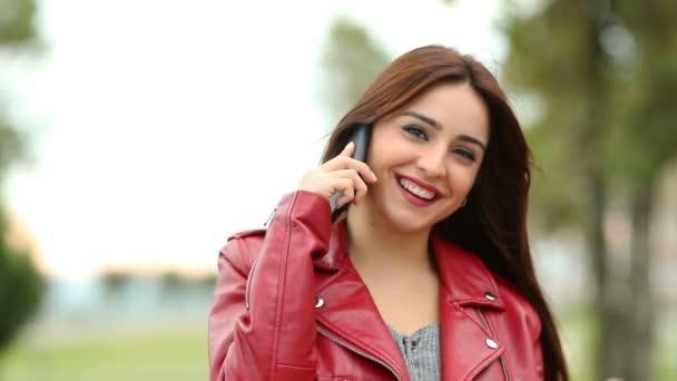 Egy őszinte nő néz rád egy parkban telefon hívás elölnézet. Lassú mozgás