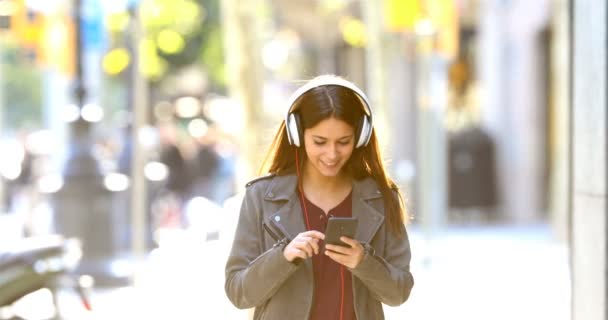 Front view of a happy teen walking towards camera listening to music in the street