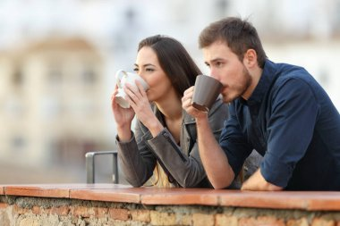 Happy couple drinking coffee watching views in a terrace