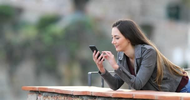 Überraschte Frau findet Smartphone-Inhalt auf Balkon einer ländlichen Wohnung