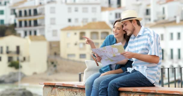 Couple of happy tourists talking and checking paper map sitting on a ledge in a coast town