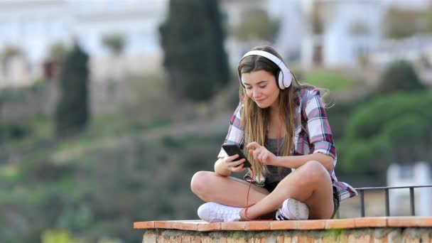 Happy teenager listening to music from a smart phone sitting on a ledge on vacation
