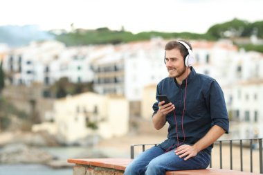 Happy man relaxing listening to music from smart phone sitting on a ledge in a coast town on vacation