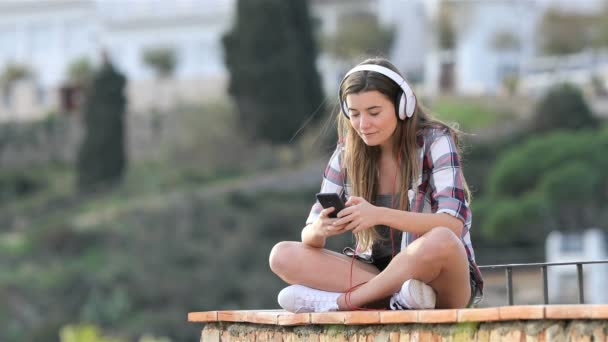 Fullbody of a happy teen listening to music and breathing fresh air relaxing sitting on a ledge in a coast town on vacation
