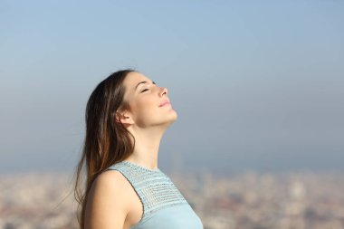 Happy woman breathing deep fresh air with a city in the background