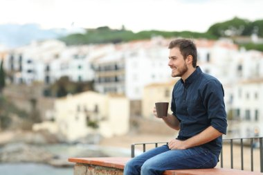 Happy man drinking coffee and looking away sitting on a ledge in a coast town on vacation