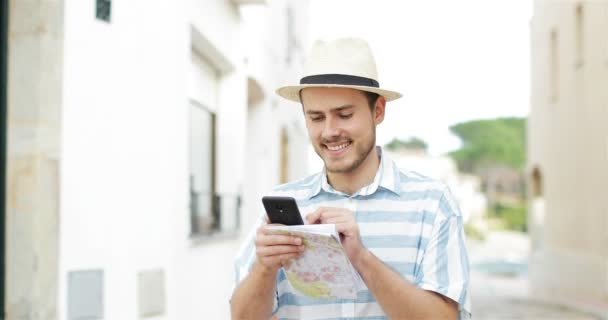 Happy tourist man browsing smart phone content walking in the street on vacation