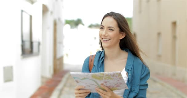 Happy tourist walking in the street checking paper map and looking at side