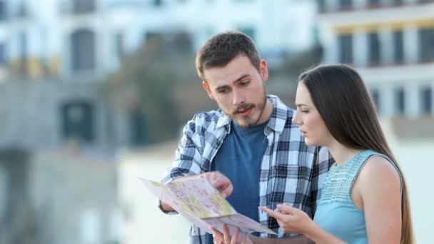 Lost couple of tourists finding best offer online on a smart phone on vacation