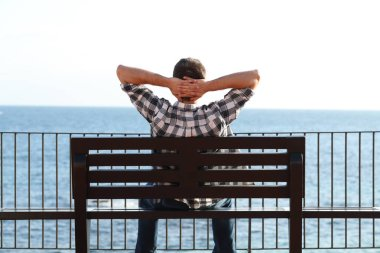 Back view portrait of a man relaxing on the beach sitting on a bench contemplating ocean