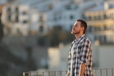 Relaxed man in a town breathing fresh air from a rural apartment balcony
