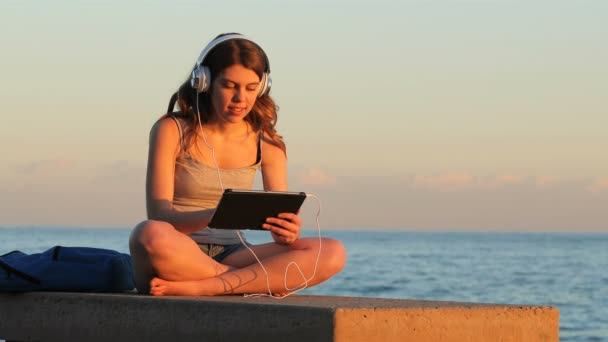 Happy teenage girl relaxing listening chill out music sitting on a bench on the beach at sunset