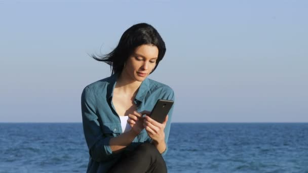 Amazed woman finding offers on smart phone sitting on a bench on the beach