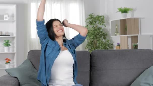 Izgatott hölgy ünnepli sikeres egyedül ül a kanapén, otthon a nappaliban