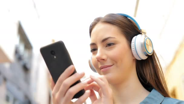 Serious woman listening to music checking songs in the street