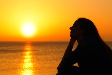 Woman silhouette watching sun at sunset on the beach