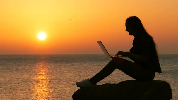 Side view portréja egy nő silhouette használ laptop napnyugtakor a tengerparton