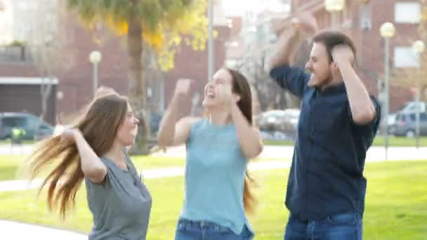 Három izgatott barátok jumping ünneplő siker az utcán