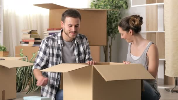 Happy couple moving home unboxing belongings sitting on the floor