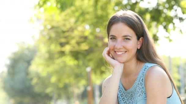 Boldog nő nevetve pózol kamera egy parkban egy napsütéses nap