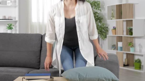 Šťastná žena odpočívá a sedí na gauči v obývacím pokoji doma
