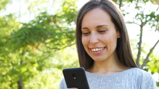 Nahaufnahme einer glücklichen erwachsenen Frau mit Smartphone in einem Park