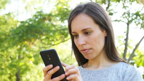 Erwachsene Frau überrascht beim Überprüfen von Smartphone-Inhalten im Park