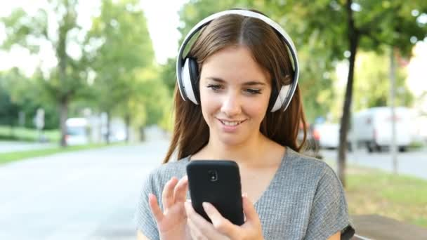 Happy woman listening to music on smart phone in the street