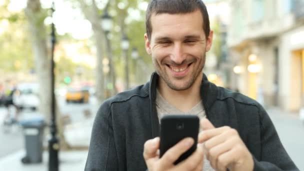 Přední pohled na šťastného dospělého muže pomocí chytrého telefonu kráčející směrem ke kameře na ulici