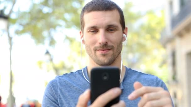 Přední pohled portrét šťastného muže kráčejícího ke kameře pomocí chytrého telefonu