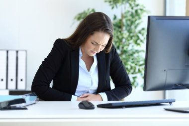 Young businesswoman suffering bellyache at office