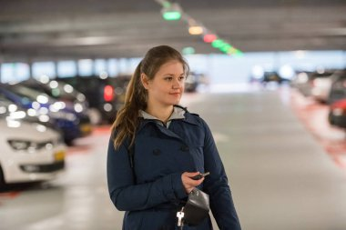 Young woman with car keys in parking garage looking for a car
