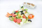 Görög, mediterrán vagy Égei zöld friss vegetáriánus saláta a Fish Restaurant asztalán. Zöld saláta a tálba olívaolajjal a Beach Fish Restaurant Görögországban vagy Törökországban.