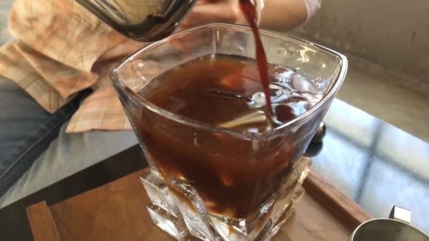 Einschenken von schwarzem Kaffee wiederverwendetes Eiswürfelgetränk, Archivmaterial
